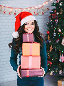 Фотографии Новый год Брюнеток Улыбка Шапки Подарки девушка