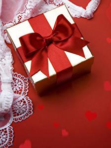 Фото День святого Валентина Красный фон Подарок Бантики Сердце