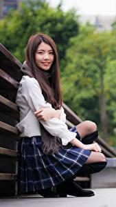 Картинка Азиатки Боке Сидит Юбки Шатенка Смотрят Улыбается молодые женщины