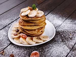 Фото Блины Бананы Сахарная пудра Тарелке Доски Еда