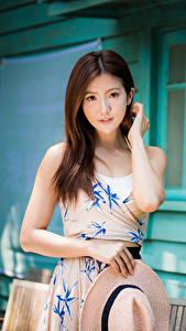 Фотографии Азиатки Платья Рука Шляпы Шатенки Миленькие Смотрит девушка
