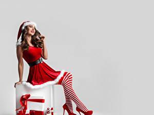 Фотография Новый год Белым фоном Шатенки Шапки Униформе Ноги Туфель Гольфах Подарков девушка