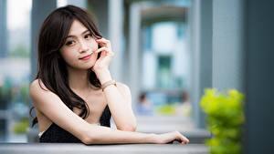 Фотография Азиатка Размытый фон Смотрят Брюнетка Волос Рука молодые женщины