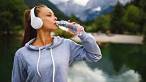 Фотографии Шатенка Наушники Бутылка Пьет воду
