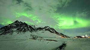 Картинка Исландия Зима Горы Небо Снега Северное сияние Облачно Природа