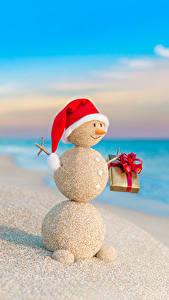 Фото Рождество Побережье Снеговика В шапке Подарки Песок