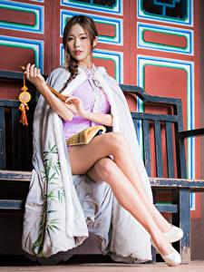 Обои для рабочего стола Азиатка Скамейка Сидя Ноги Платья Шатенка Взгляд молодая женщина