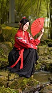 Фотография Азиатки Камень Ручеек Сидящие Кимоно Веер Смотрит девушка