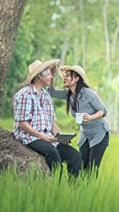 Фотография Азиаты Мужчины Две Шляпа Сидит Трава Брюнеток Девушки