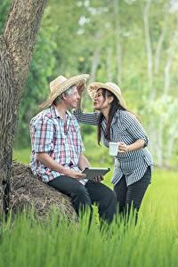 Фотография Азиаты Мужчины Двое Шляпа Сидит Трава Брюнеток Девушки