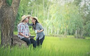 Фотография Азиаты Мужчины 2 Шляпа Сидящие Трава Брюнетка Девушки
