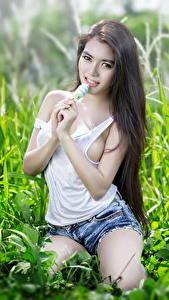 Картинки Азиатки Брюнетка Трава Взгляд Майке Шортах Рука Поза девушка