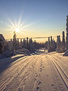 Картинка Финляндия Лапландия область Рассвет и закат Дороги Зимние Пейзаж Солнца Лучи света Снега Природа