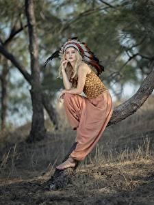 Фото Перья Индейский головной убор Блондинок Размытый фон Позирует Сидящие Деревья Индеец Vicky молодые женщины