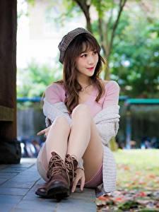 Картинки Азиатка Размытый фон Шатенки Сидя Берет Ноги Ботинка молодая женщина