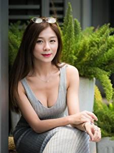 Фотографии Азиатки Позирует Рука Платья Вырез на платье Смотрит Улыбается Шатенки Сидящие девушка