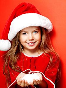 Обои Праздники Рождество Девочки Шапки Улыбка Красный фон Красивые Ребёнок