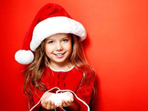 Обои Праздники Рождество Девочки Шапки Улыбается Красном фоне Красивые Дети