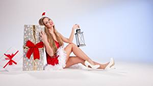 Обои Рождество Подарки Русых Униформе Сидит В шапке Бантик Лампа Ноги Туфель девушка
