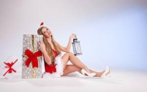 Обои Рождество Подарки Русые Униформа Сидит Шапки Бантик Лампа Ноги Туфли Девушки
