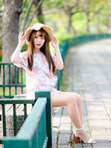 Картинки Азиатки Шатенки Сидит Платье Шляпа Ног девушка