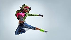 Фотографии Серый фон Блондинок Прыжок Руки Джинсов молодая женщина
