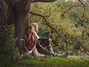 Фотографии Эльф Мужчины Хоббит Сидящие Трава Ствол дерева Косплей Юноша Legolas Tauriel LuckyStrikeCosplay молодая женщина