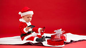 Картинки Рождество Праздники Младенец Униформа Мальчишки Подарки Телефон Красном фоне ребёнок