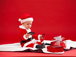 Картинки Рождество Праздники Младенец Униформа Мальчишки Подарки Телефон Красном фоне