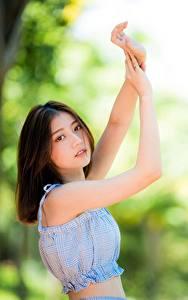 Фото Азиаты Размытый фон Рука Шатенки Смотрит девушка