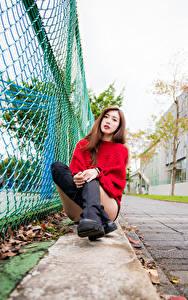 Фото Азиатка Сидящие Сапогах Ног Свитер Забор Взгляд девушка