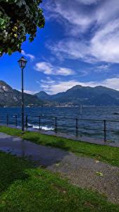 Фотография Италия Озеро Небо Пейзаж Скамейка Уличные фонари Забор Bellagio Природа
