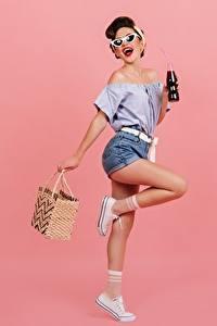 Фотографии Сумка Позирует Шатенка Очков Ноги Шортах Блузка Бутылки Розовый фон девушка