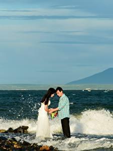Фотографии Побережье Камни Волны Мужчина Азиаты 2 Невеста Жених Свадебные Природа Девушки