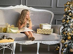 Обои Рождество Девочки Диван Сидит Подарки Новогодняя ёлка Шар Ребёнок