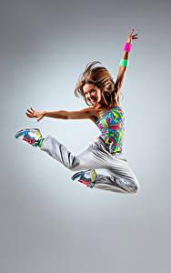 Картинки Серый фон Шатенка Прыжок Улыбка Руки Радость