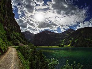 Обои Австрия Озеро Горы Леса Дороги Небо Облака Reutte District Tyrol Природа