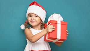 Картинки Рождество Цветной фон Девочки Шапки Подарков Улыбается Платья Дети