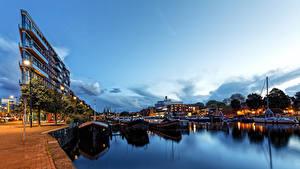 Картинки Нидерланды Амстердам Вечер Пирсы Здания Речные суда Водный канал Уличные фонари Города