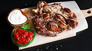 Фото Мясные продукты Черный фон Разделочная доска Кетчупом