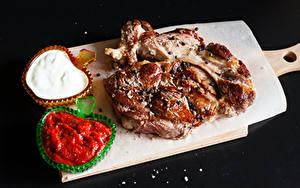 Фото Мясные продукты Черный фон Разделочная доска Кетчупом Продукты питания