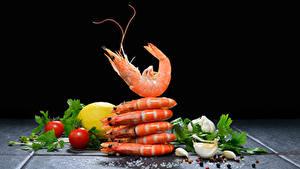 Фотографии Морепродукты Креветки Чеснок Помидоры Лимоны Перец чёрный На черном фоне Еда