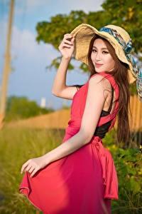 Картинка Азиатка Боке Шатенка Смотрят Шляпы Руки Платье молодые женщины