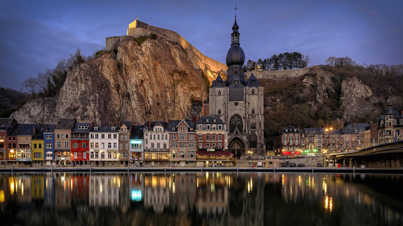 Картинки Бельгия Dinant Скала река Вечер Храмы Дома Города 1366x768 Утес скалы скале Реки речка город Здания