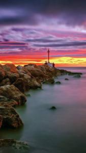 Картинка Испания Берег Рассветы и закаты Небо Камень Маяки Море Valencia Природа
