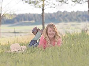 Фото Блондинки Трава Лежа Шляпы Размытый фон Улыбка молодая женщина