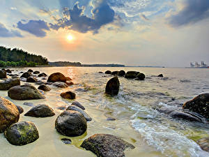 Картинка Сингапур Берег Тропический Рассвет и закат Камни Волны Природа