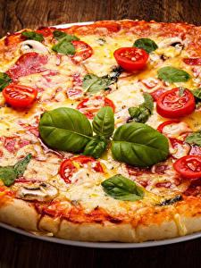 Фотографии Фастфуд Пицца Помидоры Доски Листва Базилик душистый Продукты питания