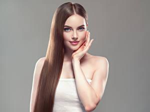 Фотографии Серый фон Шатенка Волосы Улыбка Рука Красивый девушка