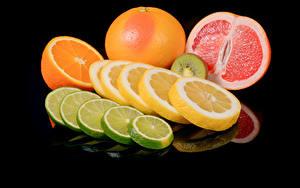 Фото Цитрусовые Лимоны Апельсин Грейпфрут На черном фоне